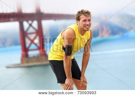 Running man - male runner resting in San Francisco listening to music on smartphone. Fit young man jogging by San Francisco Bay and Golden Gate Bridge. Jogger training to music on smart phone