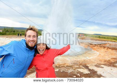 Iceland tourists fun by Strokkur geyser happy visiting famous tourist attractions and landmarks on the Golden Circle. Happy multiracial travel couple on holiday vacation sightseeing Icelandic nature.