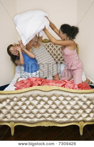 Teenage Girls pillow fighting kneeling on funky bed