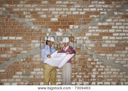 Jefe de obras y arquitecto examinar planes