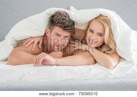 Close up Middle Age Sweet Lovers on White Bed with Cover Looking at Camera. Isolated on Gray Background.