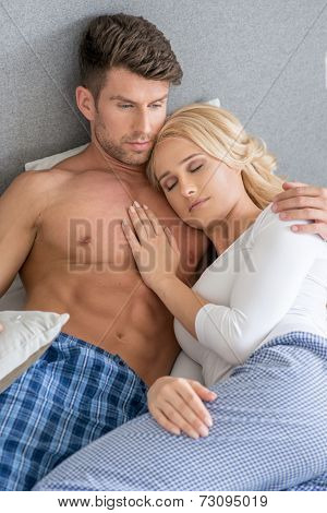 Close up Romantic Lovers on Bed Fashion Shoot. Woman is Sleeping Next to Shirtless Partner. Captured on Gray Wall Background.