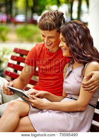 Couple with tablet pc sit on bench  . Outdoor.