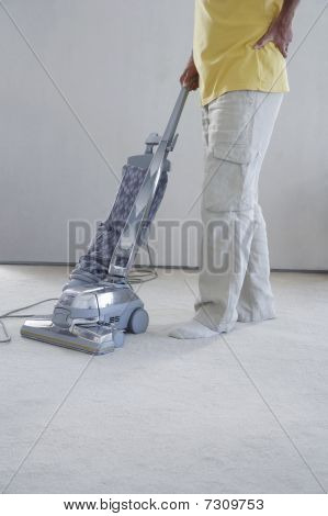 Mature man vacuuming carpet holding lower back in pain low section