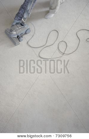 Mature woman vacuuming carpet low section