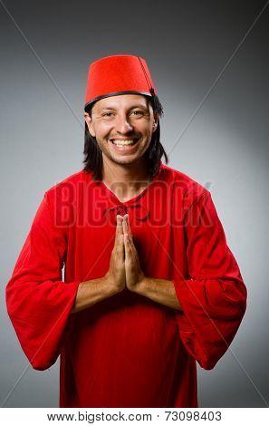 Man in red dress wearing fez hat