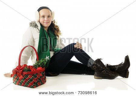 An attractive preteen sitting in winter wear with a Christmas basket filled with ornaments.  On a white background.