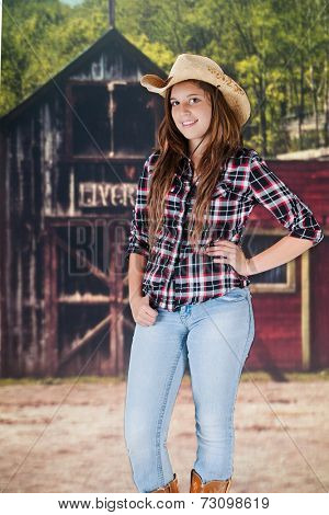 A pretty teen cowgirl standing in front of an old western livery.