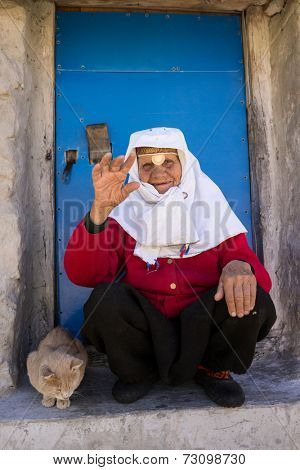 Old woman with cat in front of her home