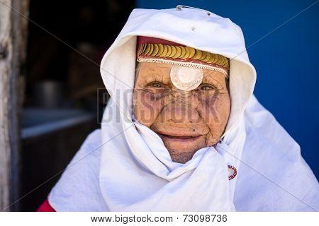 Very elderly woman wearing golden jewelry under head scarf closeup