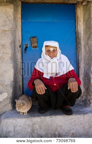 Portrait of very elderly woman wearing golden jewelry under head scarf with a cat in front of house