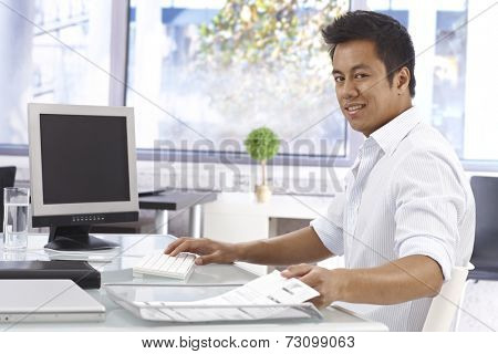 Young Asian businessman working in bright office, sitting at desk, looking at camera.