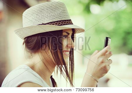 Happy young girl on countryside using smartphone