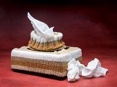stock photo of tissue box  - Tissue box in knit encasement over dark red background - JPG