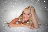 stock photo of blanket snow  - Composite image of smiling woman under a duvet against snow - JPG