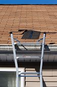 stock photo of soffit  - A ladder set up to repair damaged roof shingles - JPG