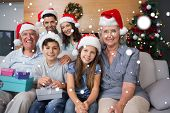 picture of extended family  - Extended family in Christmas hats with gift boxes in living room against snow - JPG