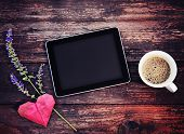stock photo of toned  - electronic tablet device on a wooden workspace table with coffee and flower toned with a retro vintage instagram filter effect  - JPG