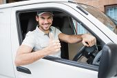 picture of thumb  - Delivery driver showing thumbs up driving his van outside the warehouse - JPG