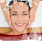 stock photo of peaceful  - Peaceful brunette enjoying a facial massage against christmas themed frame - JPG