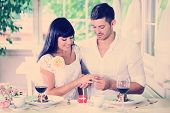stock photo of proposal  - Man proposing and holding up an engagement ring his woman over restaurant table - JPG