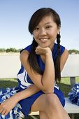 Smiling Ethnic Cheerleader sitting on bench (portrait)