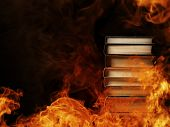 stock photo of hardcover book  - Conceptual image of a tall stack of hardcover books in a burning fire with flames and smoke swirling around them in a darkened room with copyspace - JPG