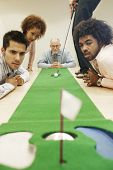 picture of miniature golf  - Group of businesspeople watching businesswoman aim golf ball - JPG