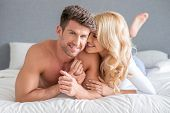 Image of sexy sweet young couple lying on white bed fashion shoot. Isolated on gray background.