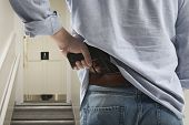 picture of bodyguard  - Bodyguard with gun protects client against an s water closet door background  - JPG