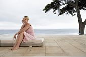 Woman sitting on sun bed by infinity pool portrait