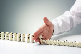 picture of change management  - Stopping the domino effect concept for business solution - JPG