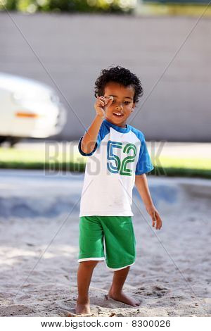 Little Boy Holding A Rock