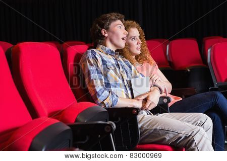 Astonished young couple watching a film at the cinema