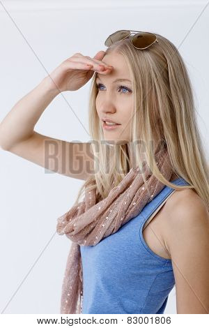 Attractive young blonde woman looking at distance at summertime.