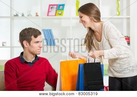 Happy couple checking shopping bags in the living room