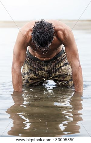 Close Up Muscled Army Kneeling On The Sea Water