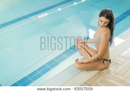 Young Woman Meditating By The Pool