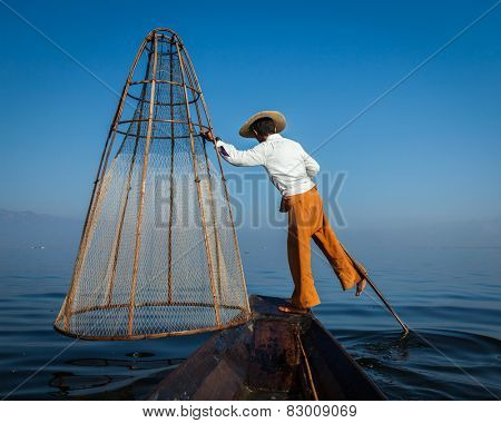 Myanmar travel attraction landmark - Traditional Burmese fisherman with fishing net at Inle lake in Myanmar famous for their distinctive one legged rowing style, view from boat