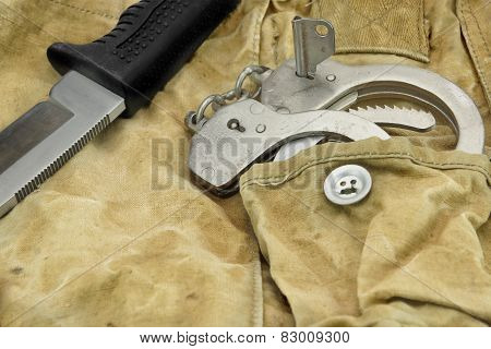 Knife And Handcuffs On The Camouflage Background