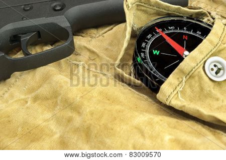 Handgun And Compass On The Weathered Backpack