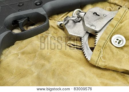 Handgun And Handcuffs On The Weathered Backpack