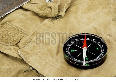 Magnetic Compass Lying Over A  Camouflage  Handbag