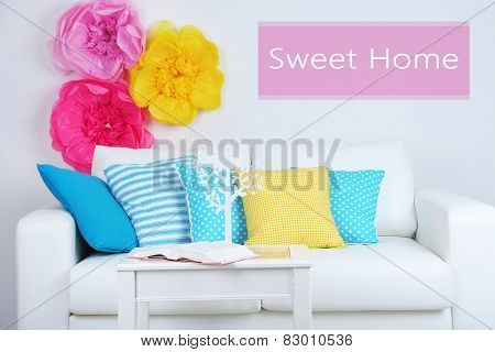 White sofa with colorful pillows in room on wall background, Sweet Home concept