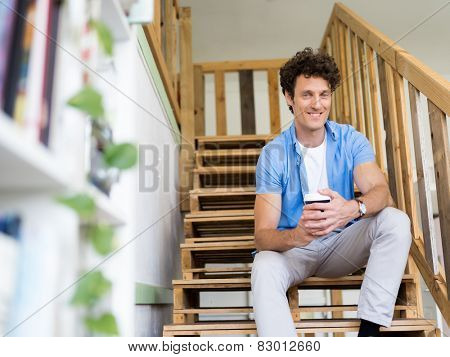 Man sitting with a mug on the stairs