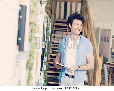 Man with a magazine standing next to bookcase