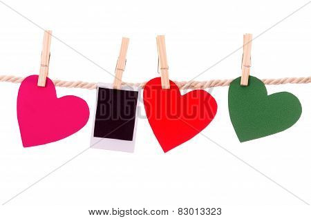 instant photograph and paper heart shapes hanging on a rope clothesline