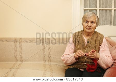Elderly woman knitting with red wool