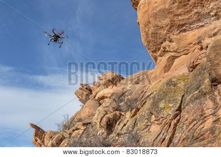 radio controlled hexacopter drone flying with a camera along sandstone canyon cliff