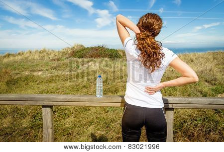 Athletic woman touching neck and back muscles by injury